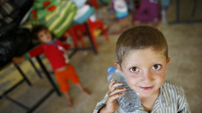 A young Syrian Kurdish refugee boy holding a bottle of water stands in the wedding hall in Suruc