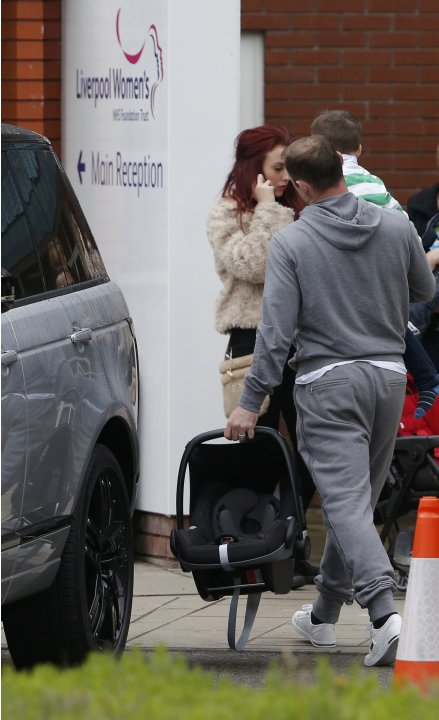Soccer player Wayne Rooney carries his son Kai at Liverpool Womens Hospital in Liverpool, Northern England