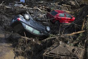 Cars are seen in the mud at a flooded zoo area in Tbilisi,…
