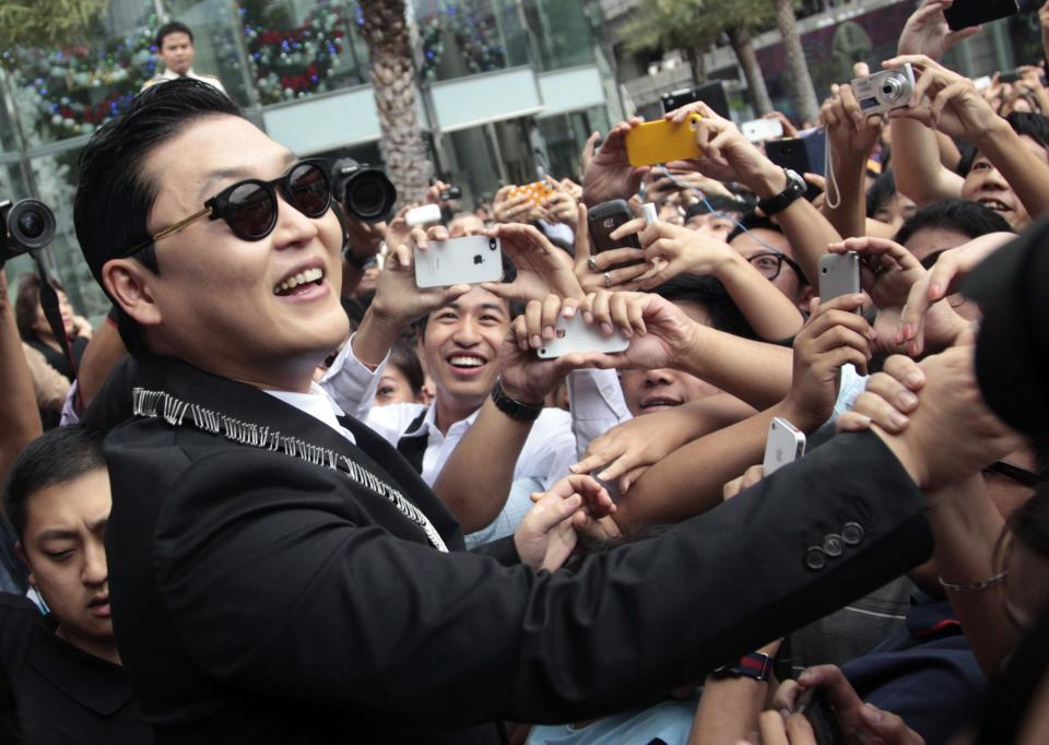 "South Korean rapper PSY, who sings the popular ""Gangnam Style,"" greets Thai fans after a press conference in Bangkok on Wednesday, Nov. 28, 2012. PSY will perform in Thailand on Wednesday night -  his first show in Asia outside of South Korea. (AP Photo/Sakchai Lalit)"