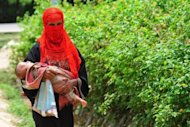 <p>A Rohingya Muslim woman walks with her child at an unregistered refugee camp in Teknaf, Bangladesh, on June 20. Myanmar's government has rejected accusations of abuse by security forces in Rakhine, after the United Nations raised fears of a crackdown on Muslims.</p>