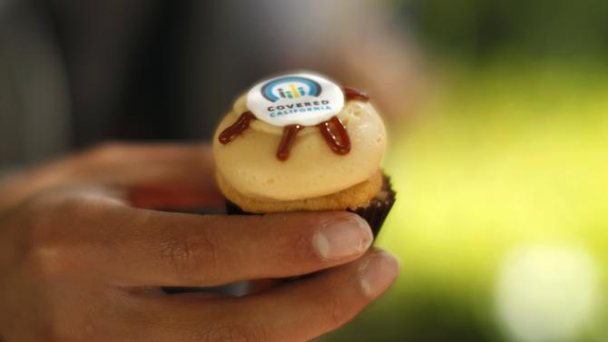 A woman holds a cupcake at a Covered California event in Los Angeles
