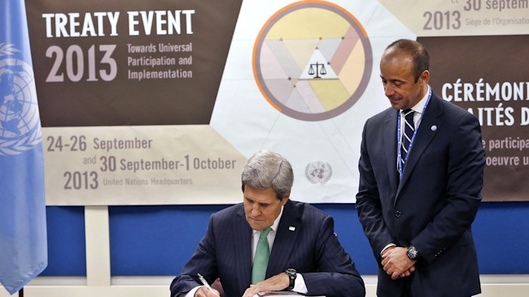 U.S. Secretary of State John Kerry signs the Arms Trade Treaty as Under Secretary-General for Legal Affairs Miguel Serpa Soares looks on during the 68th session of the United Nations General Assembly at U.N. headquarters, Wednesday, Sept. 25, 2013. (AP Photo/Jason DeCrow)