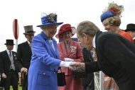 Britain&#39;s Queen Elizabeth shakes hands with a racegoer as she arrives with Prince Philip at the Epsom Derby festival in Epsom
