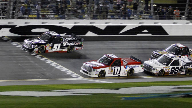Kyle Busch (51) crosses the finish line ahead of Timothy Peters (17) to win the NASCAR Truck Series auto race at Daytona International Speedway in Daytona Beach, Fla., Friday, Feb. 21, 2014. (AP Photo/Terry Renna)