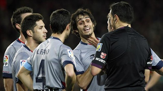Osasuna players contest a decision with the referee (Reuters)