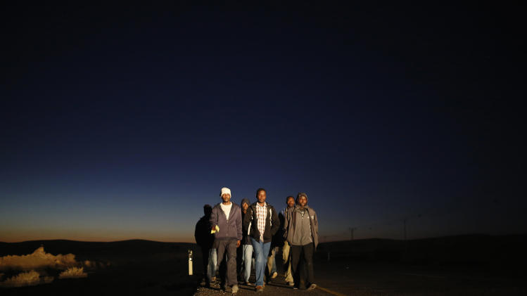 African migrants walk on a road after abandoning a detention facility in southern Israeli desert