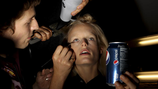 Models are readied backstage before the Diane Von Furstenberg Spring 2013 collection is modeled during Fashion Week in New York, Sunday, Sept. 9, 2012.  (AP Photo/Seth Wenig)