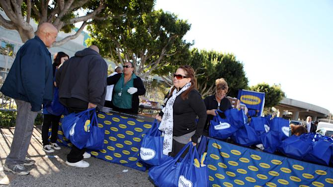 IMAGE DISTRIBUTED FOR BUTTERBALL® - Families line up at the Los Angeles Convention Center to receive 2,000 free turkeys donated by Invision for Butterball® and ARAMARK for their golden Thanksgiving meal, on Monday, Nov. 19, 2012 in Los Angeles. (Photo by Casey Rodgers/Invision for Butterball®/AP Images)