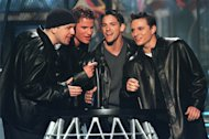 FILE - In this Oct. 28, 1999 file photo, the group 98 Degrees sings an introduction to singer Faith Hill at the WB Radio Music Awards at the Mandalay Bay Resort in Las Vegas. 98 Degrees was one of the most popular boy bands in the world, selling millions of albums and dominating the music scene in the 90s and 2000s with other groups like *NSYNC and the Backstreet Boys. (AP Photo/Laura Rauch, file)