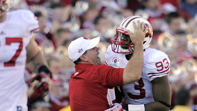 A Wisconsin coach celebrates a touchdown with Louis Nzegwu (93) during the first half of the Rose Bowl NCAA college football game against Oregon on Monday, Jan. 2, 2012, in Pasadena, Calif. (AP Photo/Mark J. Terrill)