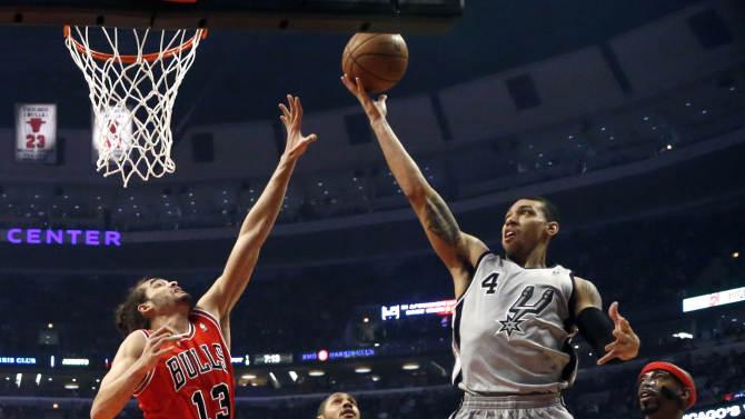 San Antonio Spurs guard Danny Green (4) drives to the basket past Chicago Bulls center Joakim Noah (13) and guard Richard Hamilton (32) as Spurs' Boris Diaw watches during the first half of an NBA basketball game, Monday, Feb. 11, 2013, in Chicago. (AP Photo/Charles Rex Arbogast)