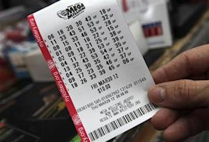 A man holds his Mega Millions lottery ticket at a shop on New York City's upper west side of Manhattan