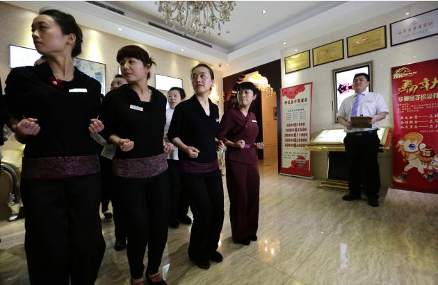 Wang Feng and her fellow masseuses wearing work suits gather for a daily morning meeting at Huaxia Liangtse Wangjing store in Beijing
