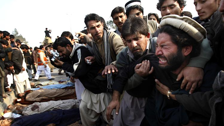 Pakistani villagers comfort a man mourning over the death of a family member, outside the governor's house in Peshawar, Pakistan, Wednesday, Jan. 16, 2013. Hundreds of villagers from northwest Pakistan protested Wednesday the killing of 18 of their relatives in an overnight raid that they blamed on security forces, displaying the bodies of the victims in the provincial capital. (AP Photo/Mohammad Sajjad)
