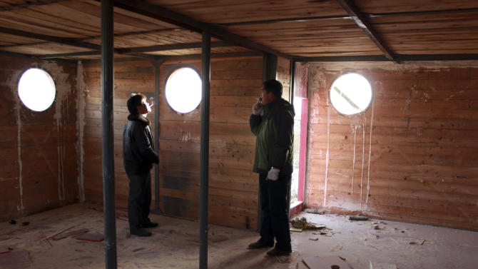 In this photo taken Nov. 24, 2012,  Lu Zhenghai, right, stands inside his ark-like vessel under construction in China's northwest Xinjiang Uyghur Autonomous Region. Lu Zhenghai is one of at least two men in China predicting a world-ending flood, come Dec. 21, the fateful day many believe the Maya set as the conclusion of their 5,125-year long-count calendar. Zhenghai has spent his life savings building the 70-foot-by-50-foot vessel powered by three diesel engines, according to state media. In Mexico's Mayan heartland, nobody is preparing for the end of the world; instead, they're bracing for a tsunami of spiritual visitors. (AP Photo/ANPF-Chen Jiansheng)