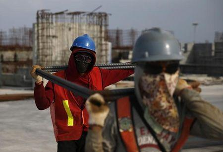 Workers carry steel bars at a construction site at a new pier in north Jakarta