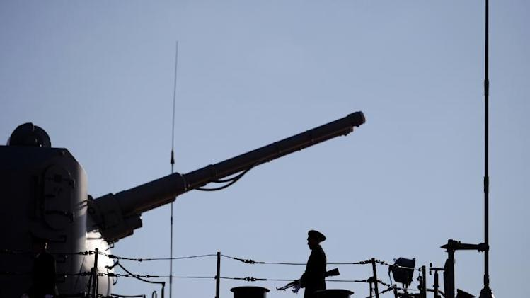 A Russian Navy member stands guard on the deck of the Pyotr Velikiy nuclear-powered missile cruiser docked in the Cypriot port of Limassol, on February 12, 2014