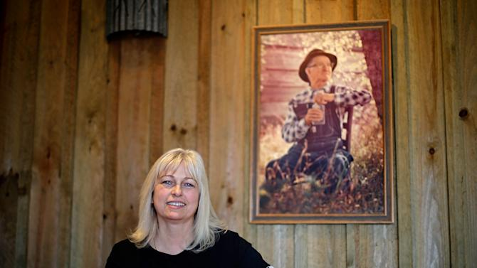 """In this Friday, Nov. 16, 2012 photo, entrepreneur Cheryl """"Happy"""" Wood stands under a portrait of her grandfather Simmie Free in the Dawsonville Moonshine Distillery, in Dawsonville, Ga. Distillers are making their first batches of legal liquor in this tiny Georgia town's hall, not far from the mountains and the maroon, orange and gold canopy of trees that once hid bootleggers from the law. (AP Photo/David Goldman)"""