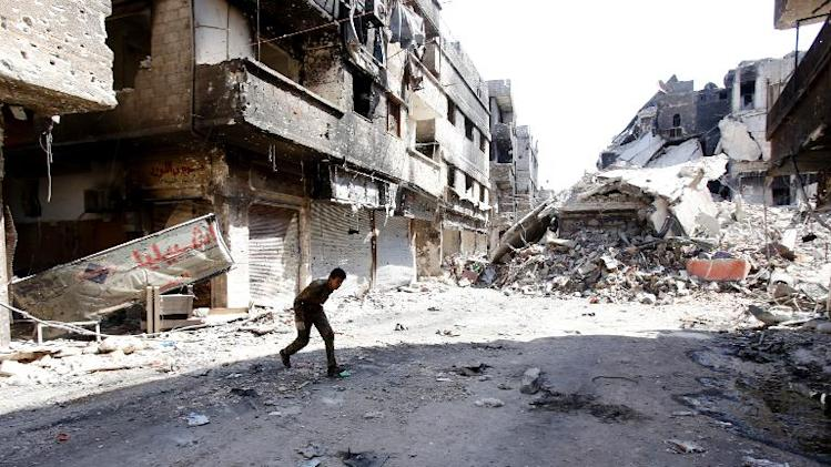A fighter runs across a street in the Yarmouk refugee camp in the Syrian capital Damascus, on September 12, 2013