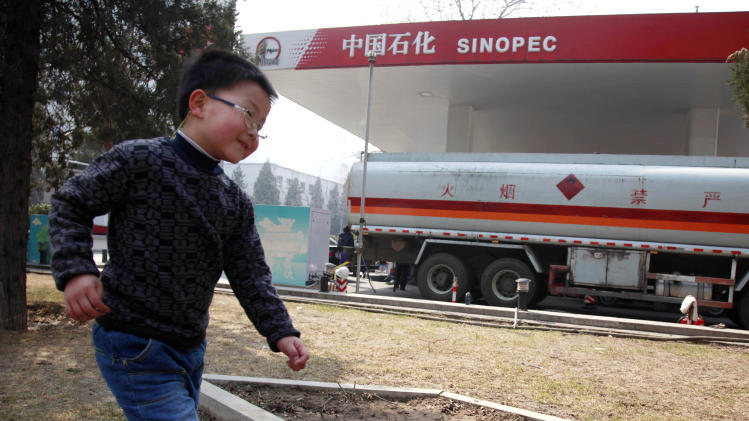 A child runs past a Sinopec gas station in Beijing Monday, March 26, 2012. Chinese state-owned oil company Sinopec said its 2011 profit rose 2 percent as price controls limited its ability to pass on higher crude costs. (AP Photo/Ng Han Guan)