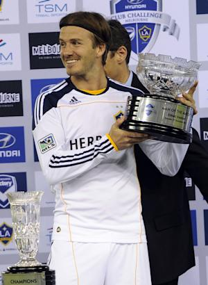 David Beckham of the LA Galaxy holds the trophy he won the Man of the Match award in their soccer friendly match against the Melbourne Victory in Melbourne, Australia, Tuesday, Dec. 6, 2011. ( AP Photo/Andrew Brownbill)
