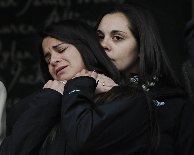 Erica Lafferty, daughter of Sandy Hook Elementary School shooting victim, Dawn Hochsprung, right, consoles Carlee Soto, sister of victim Victoria Soto after families representing fourteen families addressed the media, Monday, Dec. 9, 2013, in Newtown, Conn. Newtown is not hosting formal events to mark the anniversary Saturday. (AP Photo/Jessica Hill)