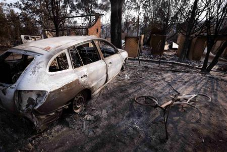 Burnt houses can be seen behind a burnt-out car and bicycle after a bushfire destroyed them in the Blue Mountains suburb of Winmalee, located around 70 km west of Sydney, October 21, 2013. REUTERS/David Gray