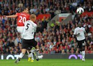 Manchester United's forward Robin van Persie (L) scores during their English Premier League football match against Fulham at Old Trafford in Manchester