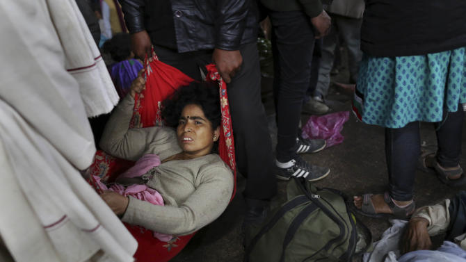 An injured Indian woman who survived a stampede on a railway platform is carried away at the main railway station in Allahabad, India, Sunday, Feb. 10, 2013. At least ten Hindu pilgrims attending the Kumbh Mela were killed and more then thirty were injured in a stampede on an overcrowded staircase, according to Railway Ministry sources.  (AP Photo/Kevin Frayer)