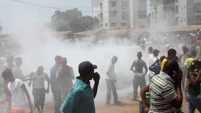 Opposition protesters disperse after tear gas is fired in their midst, in Conakry, Guinea, Wednesday, Feb. 27, 2013. Officials say security forces fired tear gas, after protests turned violent when opposition marchers started throwing stones in Guinea's capital. Government spokesman Albert Damantang Camara said Wednesday that at least 18 security personnel were injured. Opposition spokesman Mouctar Diallo said at least 9 Guineans were also injured. (AP Photo/Youssouf Bah)