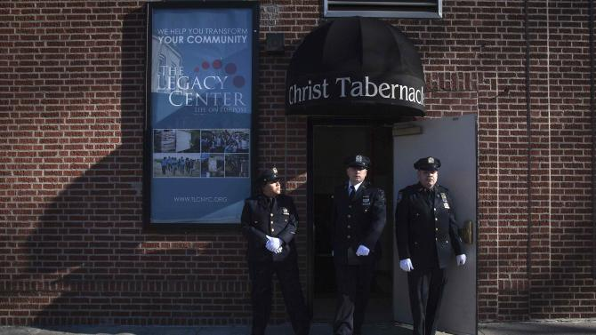 Police officers stand guard at a side door during NYPD officer Rafael Ramos' wake at Christ Tabernacle Church in the Queens borough of New York