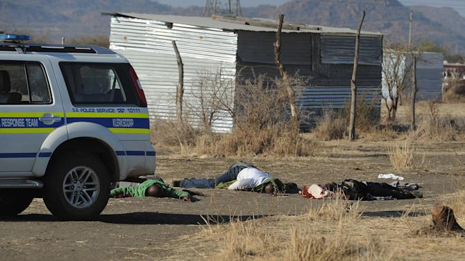 Bodies of striking miners lay on the ground after police opened fire on a crowd  at the Lonmin Platinum Mine near Rustenburg, South Africa, Thursday, Aug. 16, 2012. South African police opened fire Thursday on a crowd of striking workers at a platinum mine, leaving an unknown number of people injured and possibly dead. Motionless bodies lay on the ground in pools of blood.  (AP Photo)