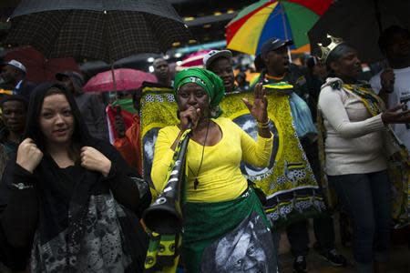 A woman plays a vuvuzela while others sing and dance at a mass memorial for Mandela in Johannesburg