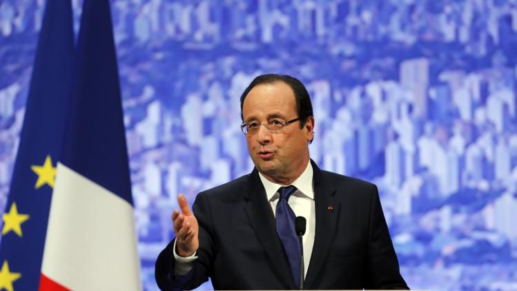France's President Francois Hollande gestures as he gives a speech during a meeting with the French community in Sao Paulo