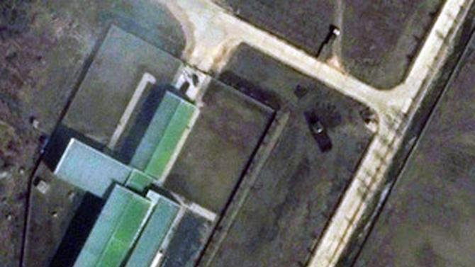 """This March 28, 2012 satellite image provided by DigitalGlobe shows a parked trailer and dish antenna, top right,  near the assembly building at North Korea's Tongchang-ri Launch Facility, on the nation's northwest coast. An analysis of images provided to The Associated Press by the U.S.-Korea Institute at Johns Hopkins School of Advanced International Studies shows Pyongyang """"has undertaken more extensive preparations for its planned April rocket launch than previously understood.""""   (AP Photo/DigitalGlobe) MANDATORY CREDIT, NO SALES"""