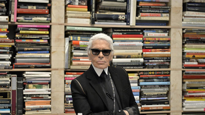 FILE - In this Feb. 14, 2014 file photo, fashion icon Karl Lagerfeld poses for photographers in front of his books prior to the start of an exhibition at the museum Folkwang in Essen, Germany. Lagerfeld and a Macau casino operator announced plans Friday, March 7, 2014 for the Chanel designer to create his first hotel. The 270-room Karl Lagerfeld Hotel will open in 2017 in a 20-story tower in the gambling enclave in southern China, according to Lagerfeld and the Sociedade de Jogos de Macau. (AP Photo/Martin Meissner, File)