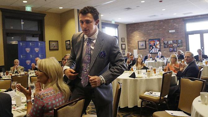 Heisman Trophy winner and Texas A&M's Johnny Manziel gets up to receive the Manning Award, as the nation's top quarterback, during a luncheon, Thursday, May 2, 2013, in New Orleans. (AP Photo/Gerald Herbert)