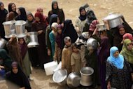 File photo shows Egyptian women waiting to fill their containers with drinking water at al-Rahawe village. A rapidly worsening water shortage threatens to destabilize the planet and should be a top priority for the UN Security Council and world leaders, a panel of experts said in a report Monday