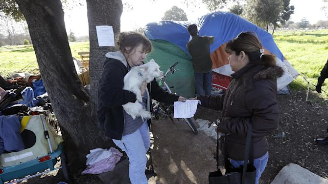 Wendy Clarke, left, holds her neighbor's dog Hero as she is handed an eviction notice by San Jose city worker Rita Tabaldo as city worker Mark Ruffing, center, attaches a notice to a Clarke's tent at a tent city in San Jose, Calif., Tuesday, March 5, 2013. The Silicon Valley is adding jobs faster than it has in more than a decade as the tech industry roars back. Stocks are soaring and fortunes are once again on the rise. But a more ominous record is also being set this year: food stamp participation just hit a 10 year high, African American wages fell 18 percent in two years and median incomes fell throughout the region. Simply put, while the ultra rich are getting even ultra richer, record numbers of Silicon Valley residents are slipping into poverty. (AP Photo/Jeff Chiu)