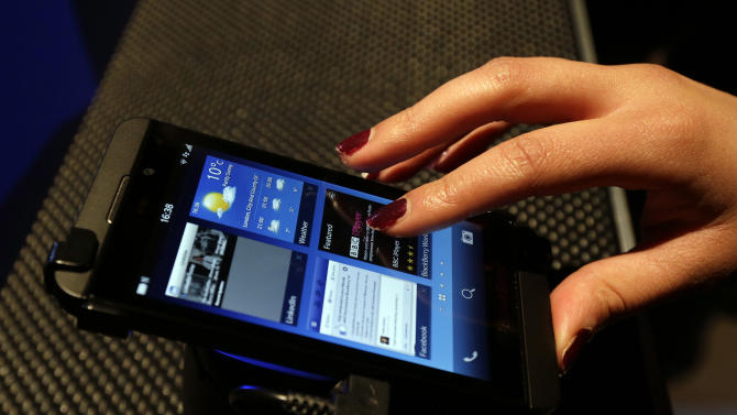 A woman uses a new touchscreen BlackBerry Z10 smartphone, put on display during a launch event for the new phone in London, Wednesday, Jan. 30, 2013. (AP Photo/Lefteris Pitarakis)