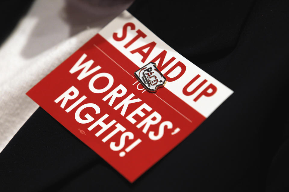 "A Pennsylvania College Democrats pin is seen on a ""Stand Up Workers Rights!"" card, on a delegate attending the Democratic National Committee winter meeting in Washington, Saturday Feb. 26, 2011. (AP Photo/Jose Luis Magana)"
