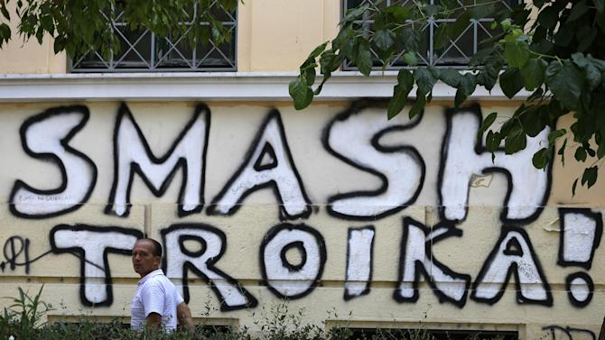 A pedestrian passes graffiti referring to the officials from the European Union, European Central Bank and International Monetary Fund, together known as the troika, in Athens, Wednesday, July 29, 2015. Representatives of Greece's creditors, its European Union partners and the International Monetary Fund, are currently meeting officials in Athens to discuss the terms of the new bailout, designed to provide 85 billion euros over three years. (AP Photo/Thanassis Stavrakis)
