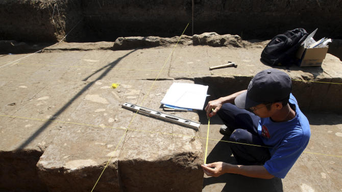 A Balinese archaeologist measures a stone of ancient temple structure in Denpasar, Bali, Indonesia on Friday, Oct. 26, 2012.  Wayan Swantika of the local archaeology agency says workers digging a drainage basin last week in eastern Denpasar, Bali's capital, at first discovered a large stone about 1 meter (3 feet) underground. (AP Photo/Firdia Lisnawati)
