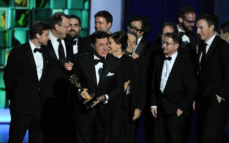 "Stephen Colbert, foreground, and the cast and crew of ""The Colbert Report"" accept the award for outstanding writing for a variety series at the 65th Primetime Emmy Awards at Nokia Theatre on Sunday Sept. 22, 2013, in Los Angeles. (Photo by Chris Pizzello/Invision/AP)"