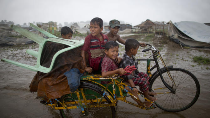 Internally displaced Rohingya man pushes a rickshaw with children and belongings leaving a camp for displaced Rohingya people in Sittwe, northwestern Rakhine State, Myanmar, Thursday, May 16, 2013. Members of the displaced Rohingya minority started to evacuate for safer shelters ahead of the arrival of Cyclone Mahasen. (AP Photo/Gemunu Amarasinghe)