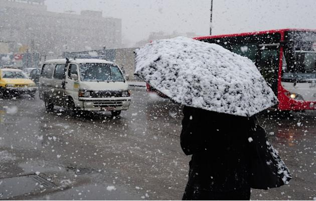 A Syrian woman walks through central Damascus during snow fall on January 9, 2013 as a fierce storm whipped the region this week and temperatures dropped dramatically.   AFP PHOTO/ STR