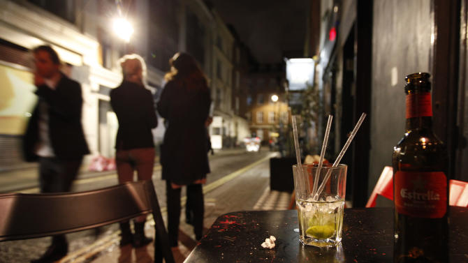 Two young women smoke outside a bar in the central London area of Soho late Friday, April, 21, 2012.  Binge drinking has reached crisis levels in Britain, health experts say, costing the cash-strapped National Health Service 2.7 billion pounds (US$4.4 billion) a year, including the cost of hospital admissions related to booze-fueled violence and longer-term health problems. Unlike all other major health threats, liver disease is on the rise in Britain, increasing by 25 percent in the last decade and causing a record level of deaths, according to recent government figures.  (AP Photo/Alastair Grant)