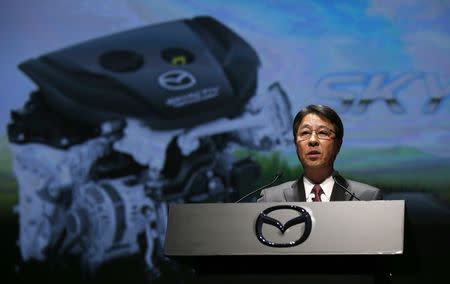 Mazda Motor Corp President and CEO Kogai Kogai speaks in front of a screen showing the company's Skyactiv-D 1.5-liter clean diesel engine during a news conference to announce the Mazda CX-3 compact crossover SUV in Japan in Tokyo