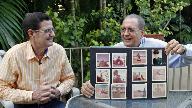 Julio De-Castro Toirac, right, shows his photo album during his years in the U.S. Army as his brother Jose Ignacio Castro Toirac, left, looks on in Coral Gables, Fla., Thursday, Oct. 11, 2012. Unbeknownst to one another, Julio and Jose Castro had both enlisted in the military, the older brother with the United States, the younger with Cuba. As the U.S. and the Soviets inched closer to catastrophe 50 years ago this week, one brother stood in the trenches in Cuba while the other awaited orders in Miami. (AP Photo/Alan Diaz)